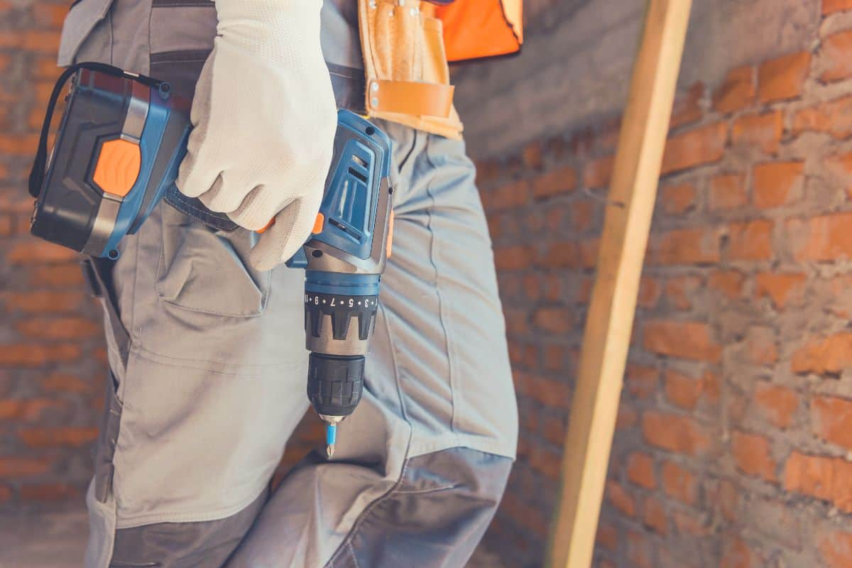 A person holding a cordless hammer drill on a job site
