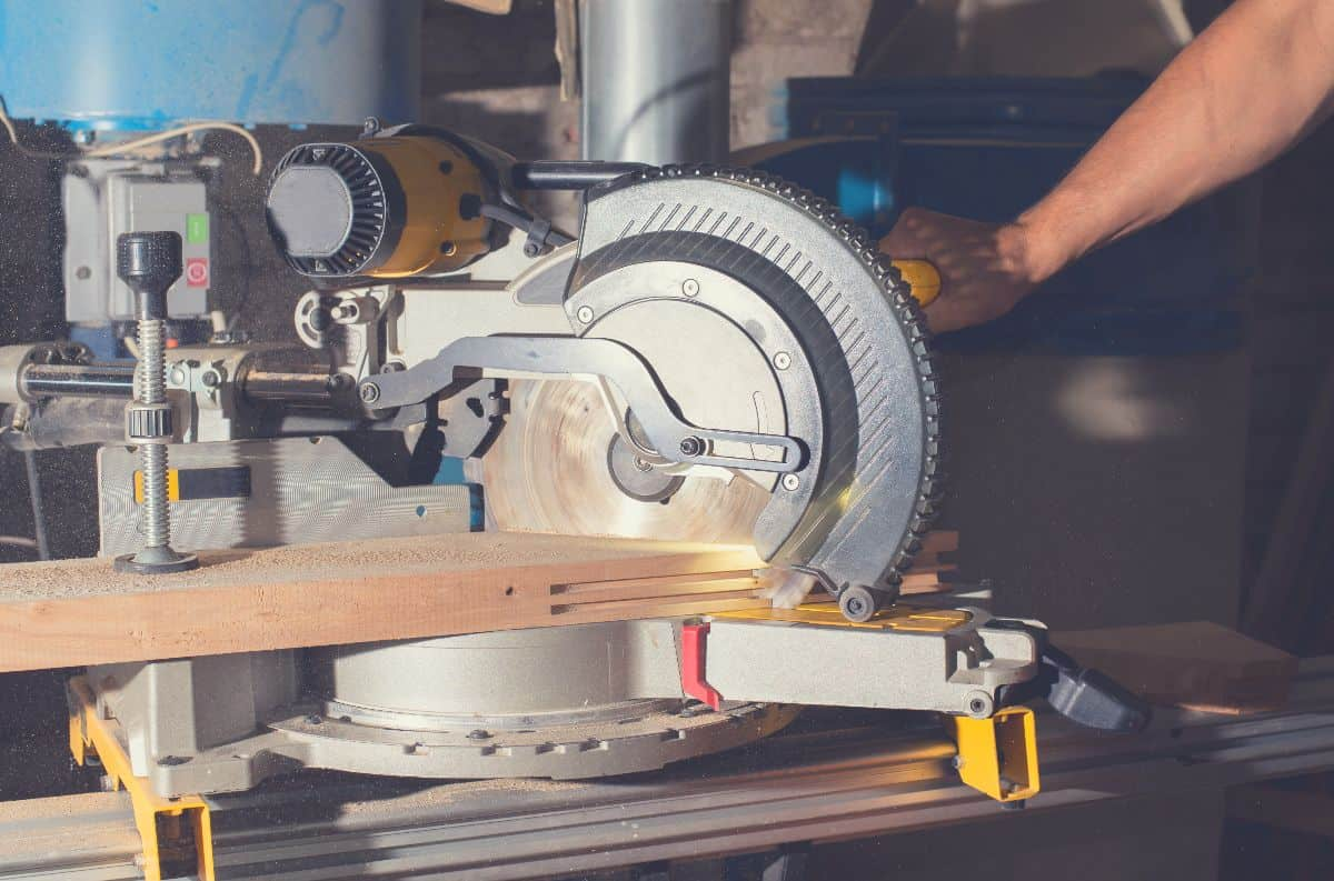 Close up of someone using a miter saw mounted on a stand