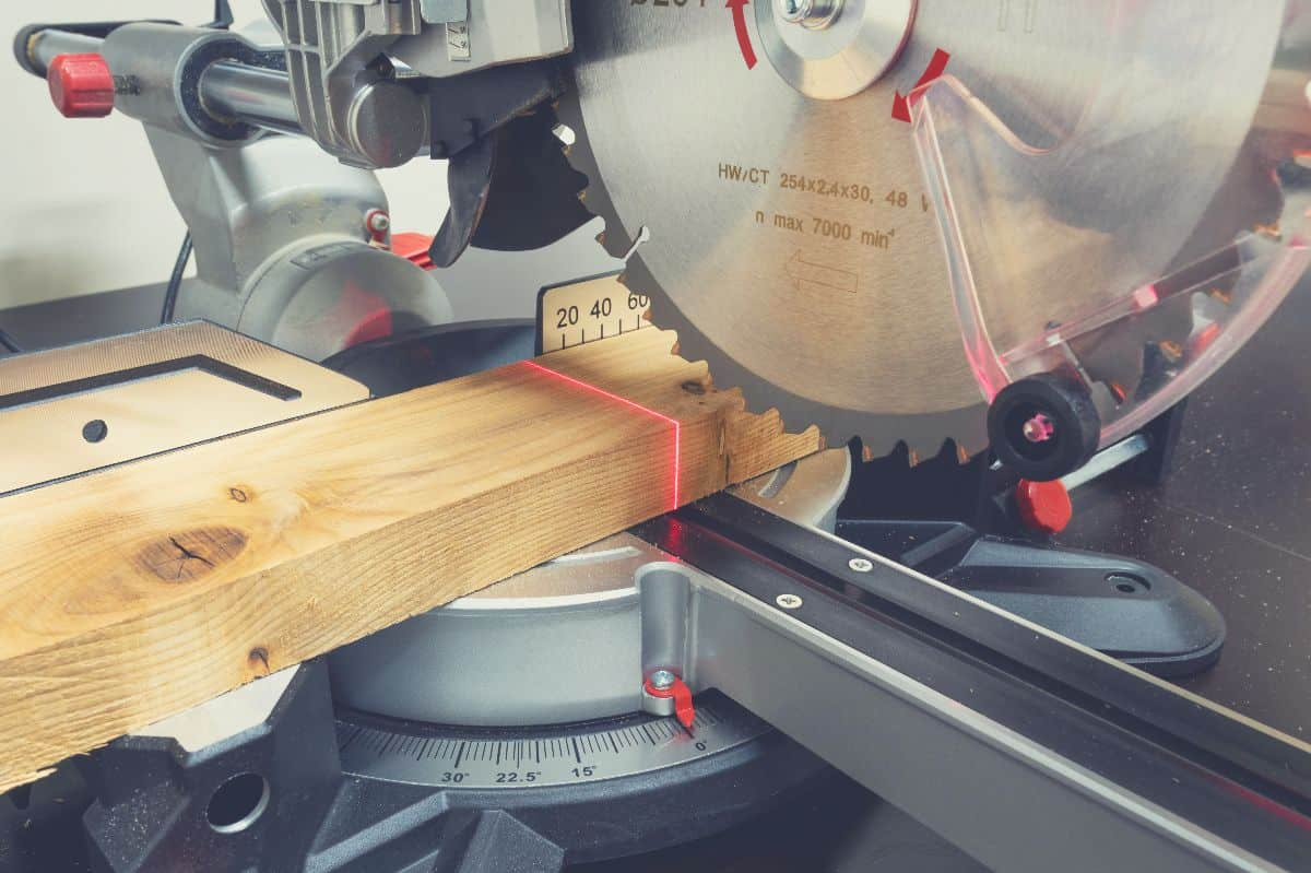 A miter saw blade set up to make a cut in a piece of wood