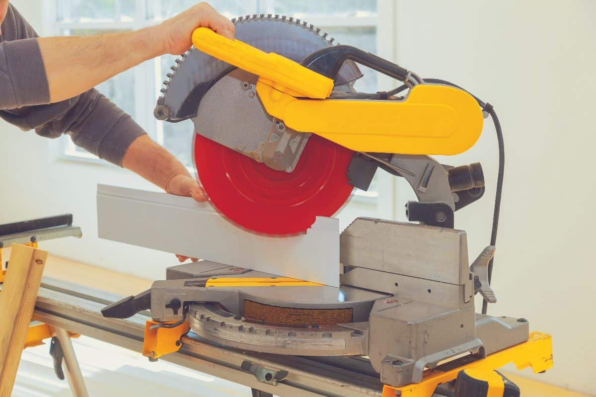 A man cutting a tall piece of baseboard using a miter saw.