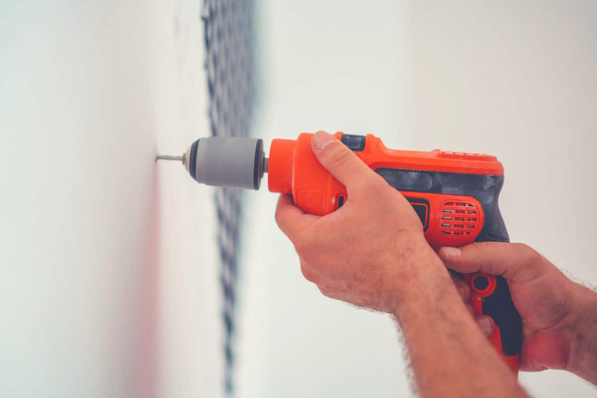 Someone drill a hole in a wall with a corded drill