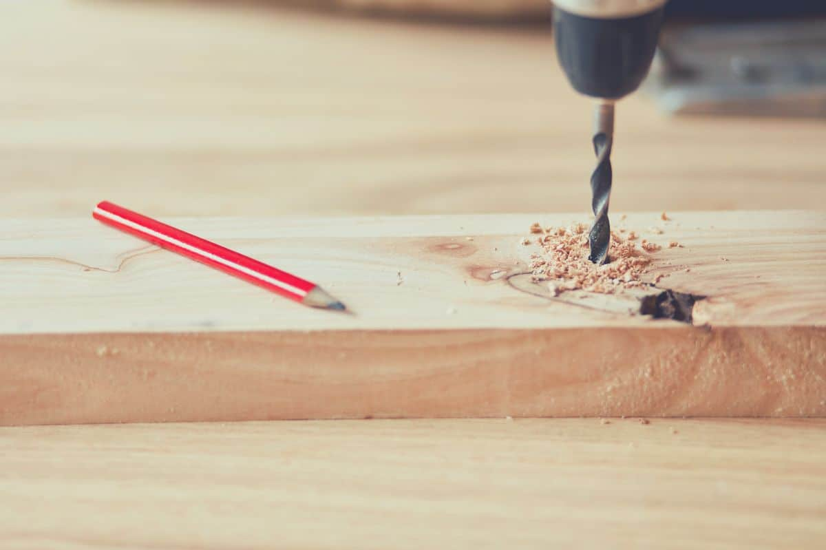 A Carpenter drilling into a piece of wood with a drill