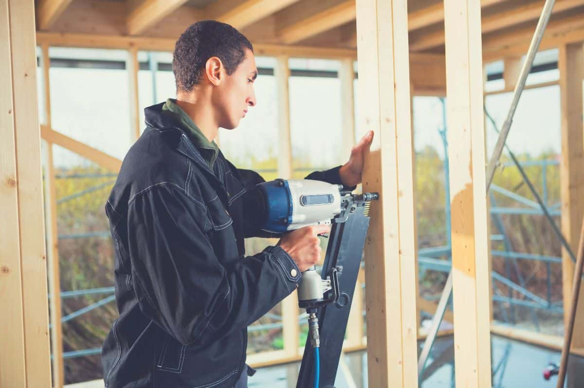 Man using nail gun on timber framing