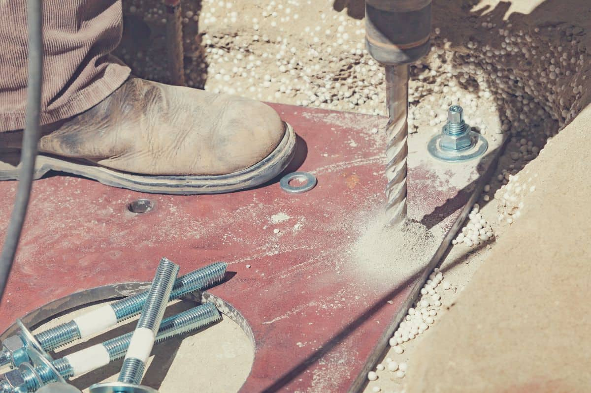 A builder drilling holes into concrete for bolt anchors