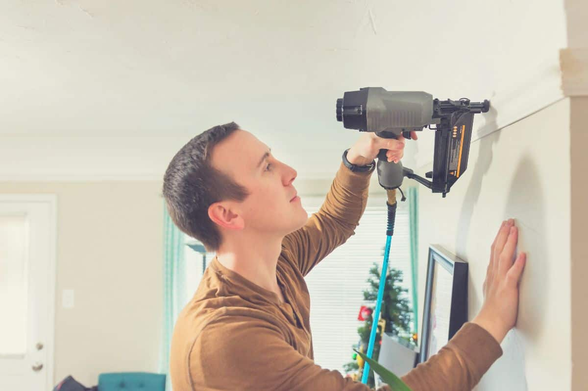 A man fitting some wall trim with a brad nailer