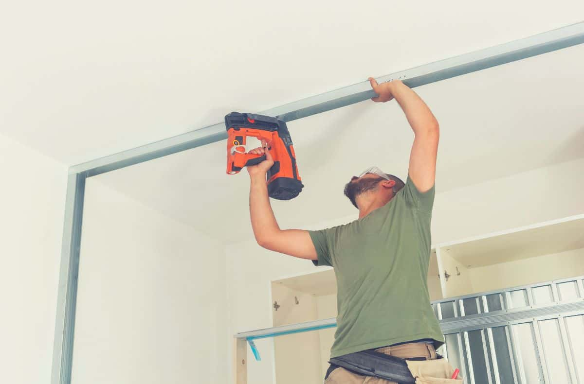Man installing trim using a cordless electric nail gun