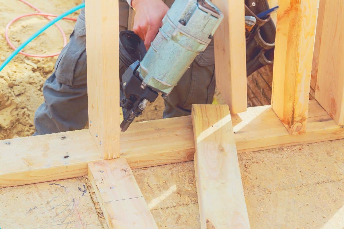 A construction worker erecting a timber frame with a framing nailer