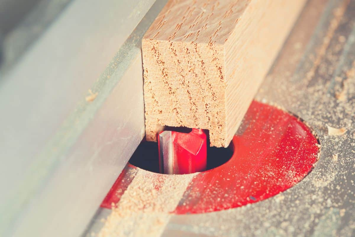 A close up of a router bit cutting wood on a router table