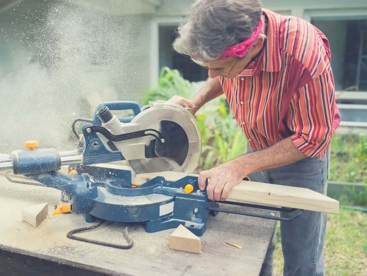 Man using sliding compound miter saw in his yard