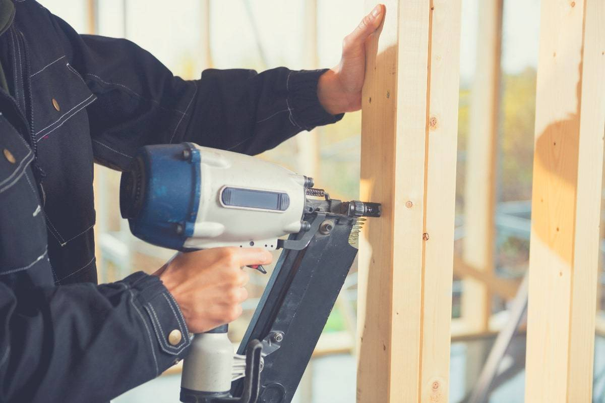 A man using a framing nailer to drive nails into a timber frame
