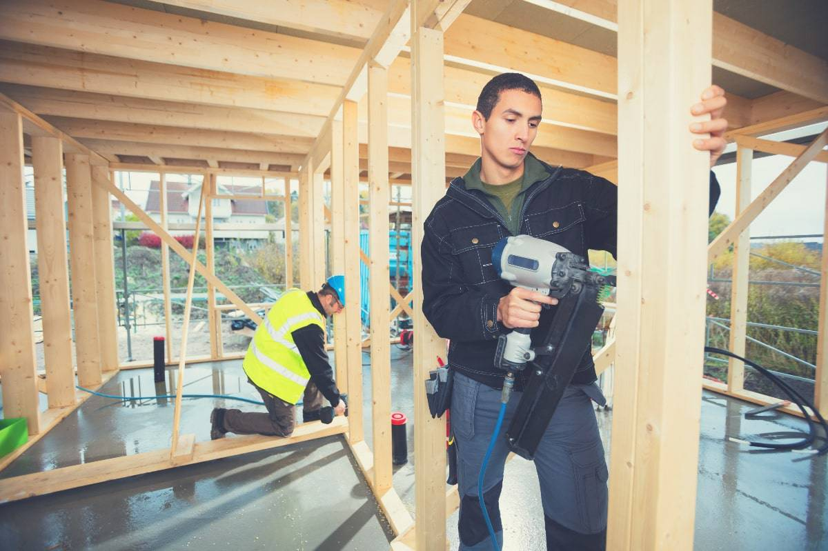 A man on a construction site using a framing nailer to drive nails into a timber frame.