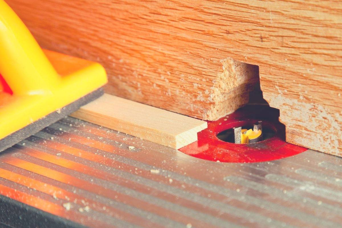 A close up image of a workpiece being fed through a router bit on a router table