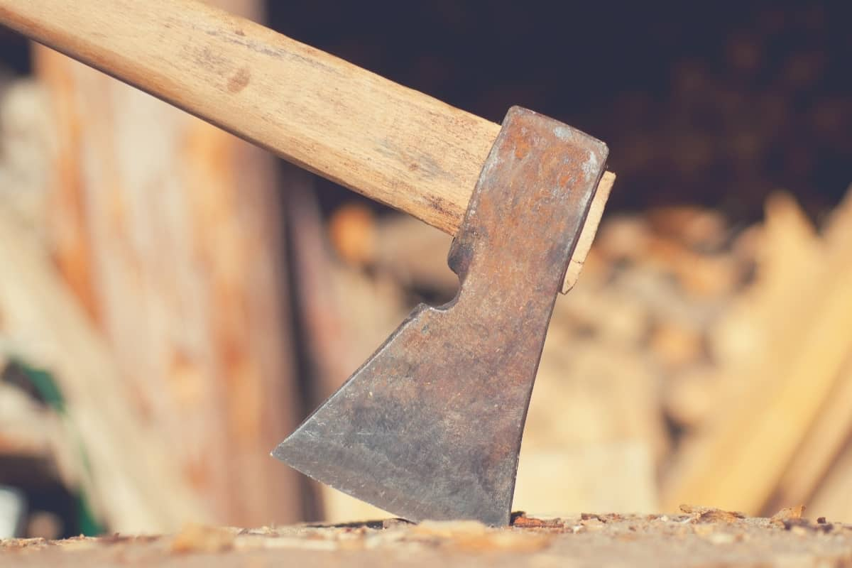 An axe stuck into a piece of wood.