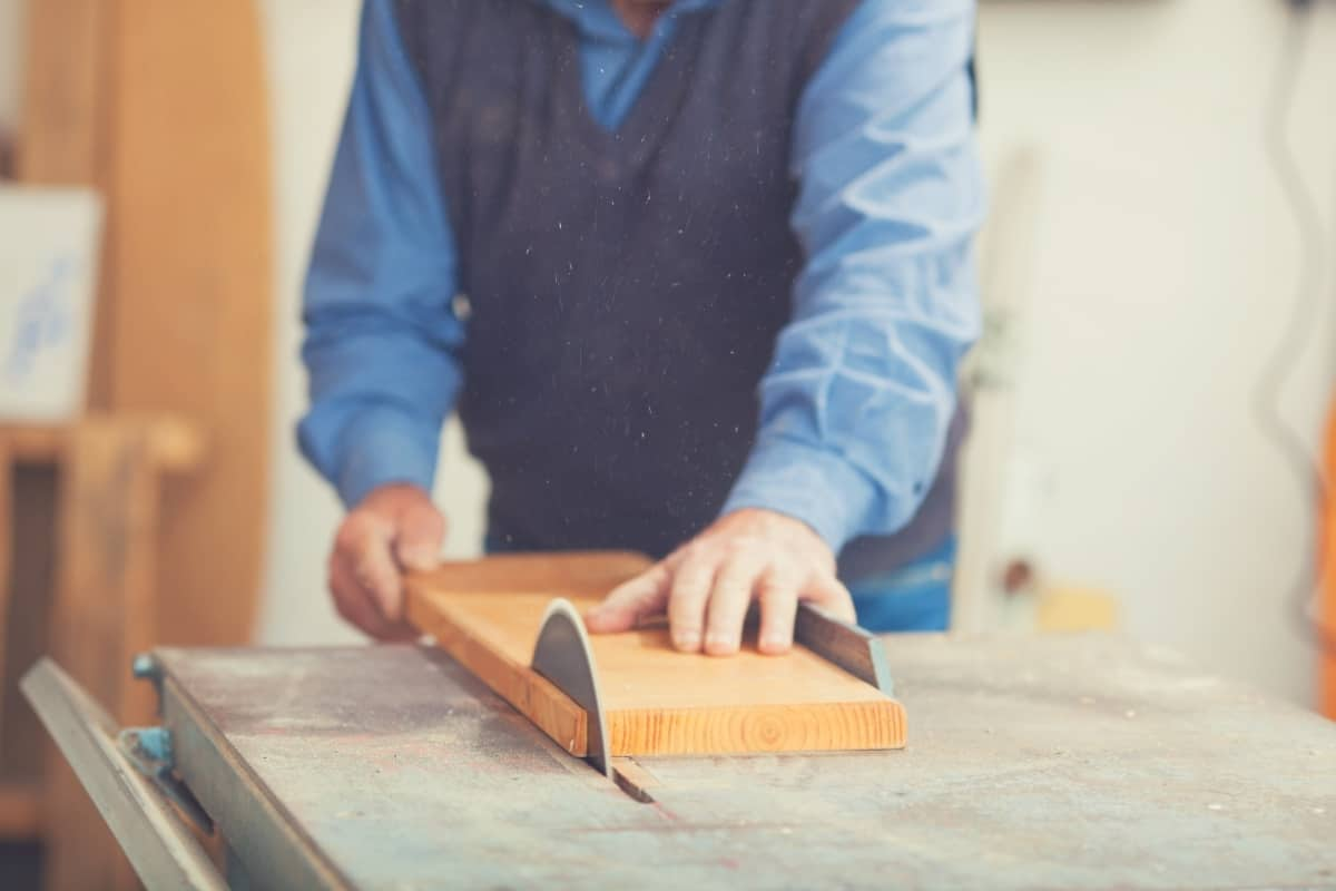 A man ripping a wooden board using a table saw
