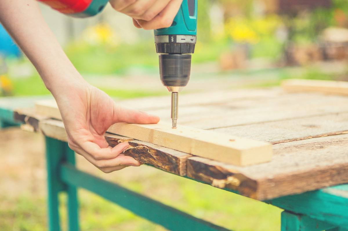 A man using an impact driver to screw pieces of wood together.