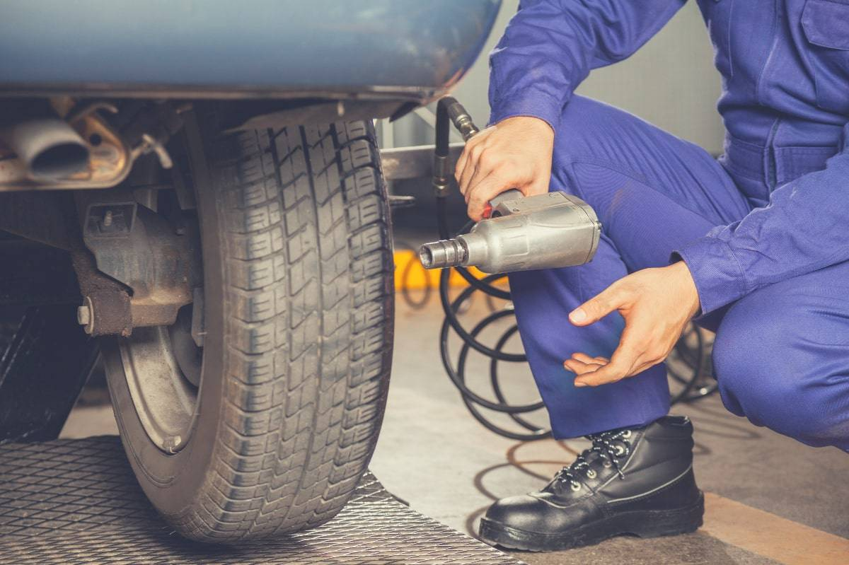 A man using an impact wrench to tighten some car wheel lug nuts.