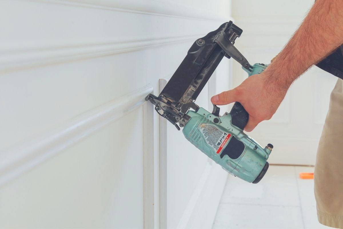 A man using a brad nail gun to attach some trim to a wall.