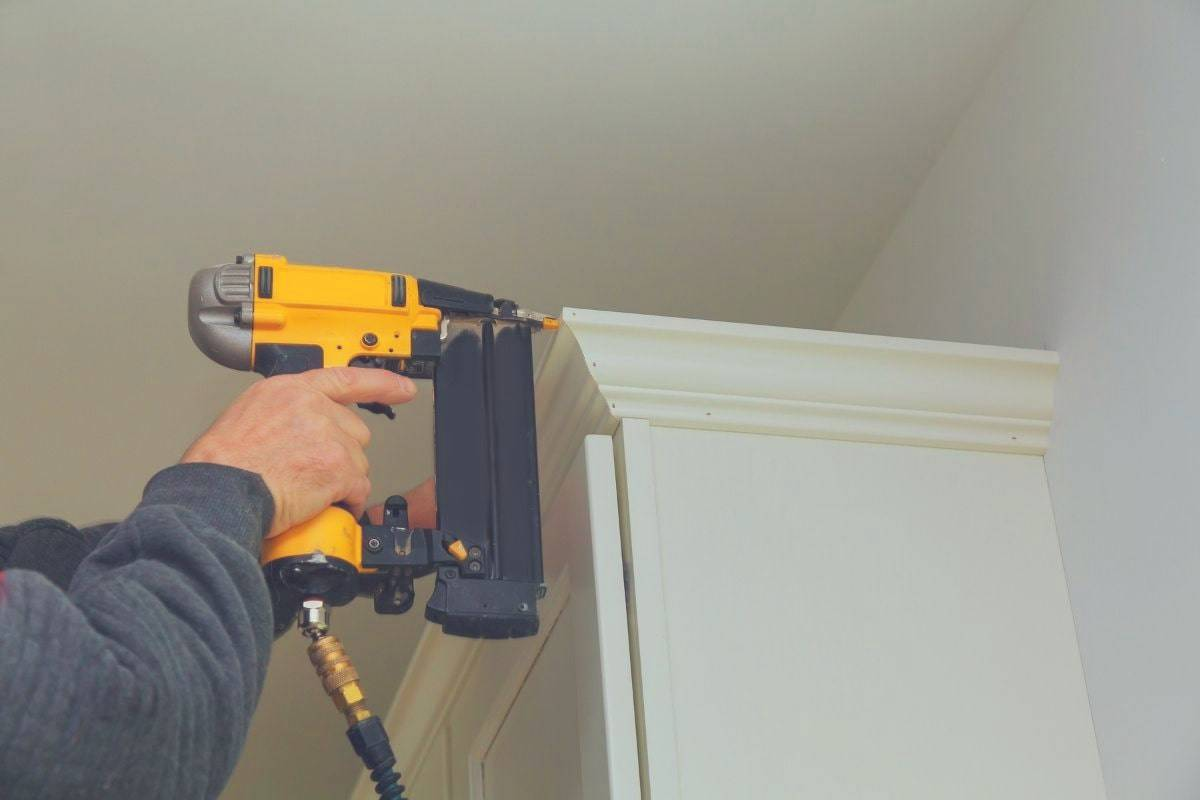 A man using a finishing nail gun to attach some trim to a cupboard.