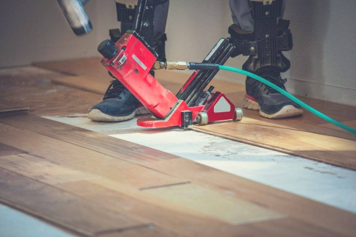 A man using a flooring nail gun to install tongue and groove solid wood flooring.