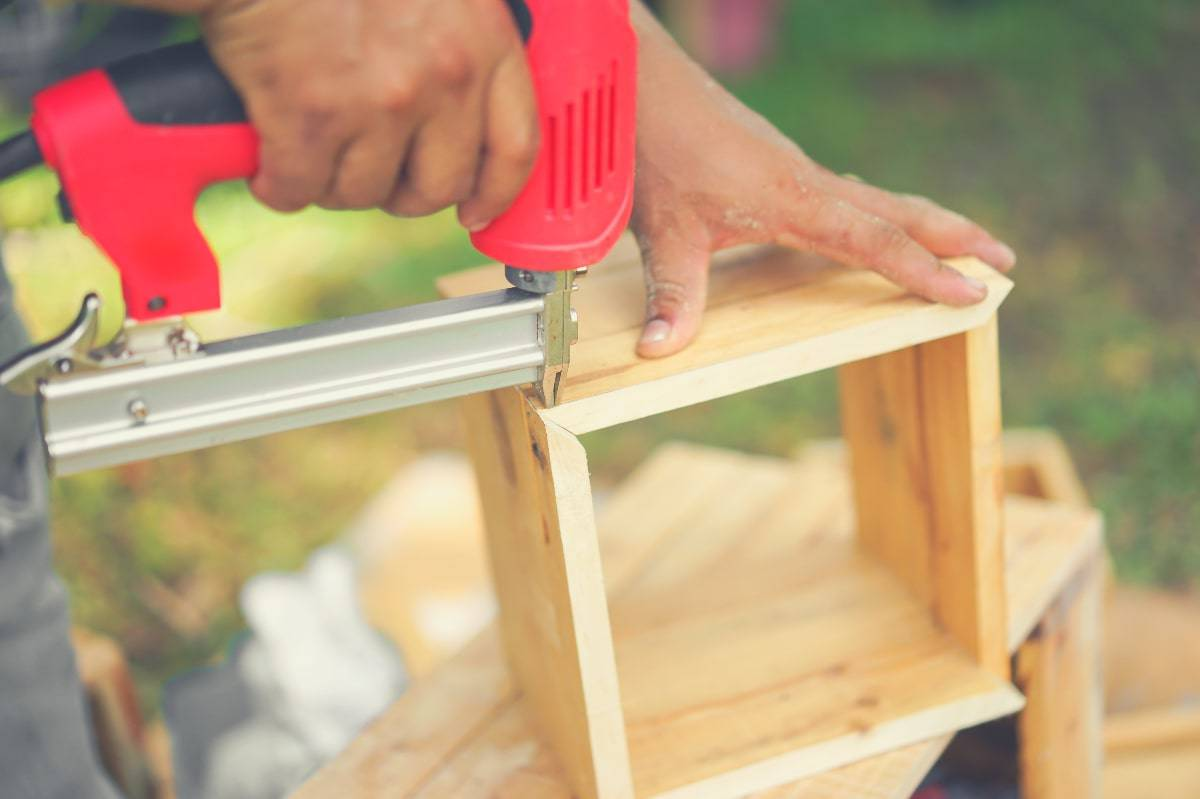 A person using a pin nail gun to fix the corners of a small wooden box