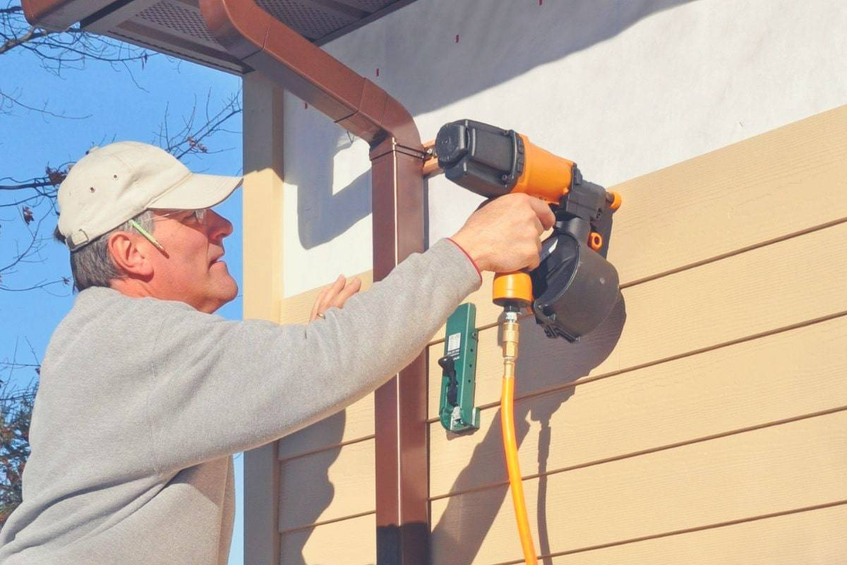 A man using a siding nail gun to install wooden siding to a house.