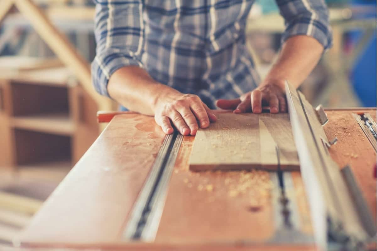 An image of a man ripping a wooden board on a hybrid table saw