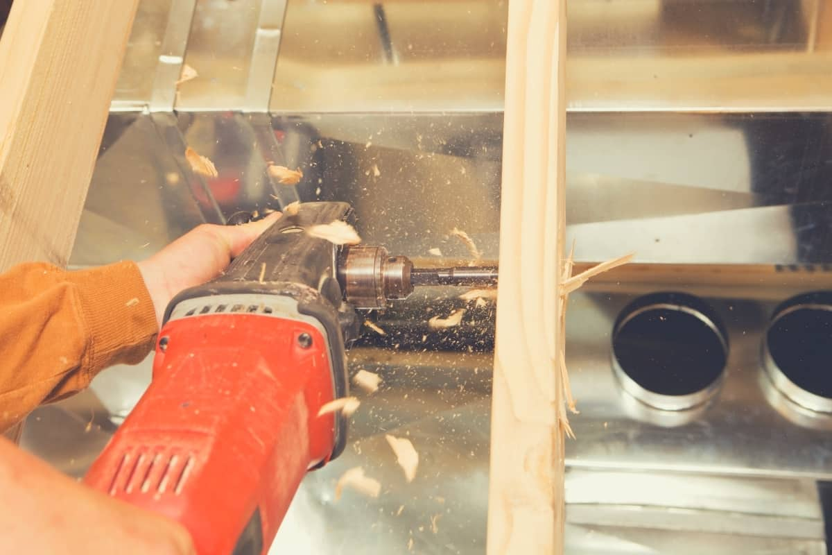 A carpenter drilling a hole in some tight framing using a right angled drill