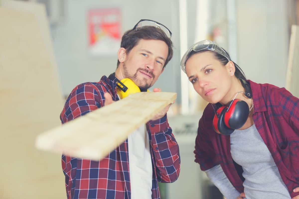 A male and a female carpenter checking to see if a piece of wood is straight