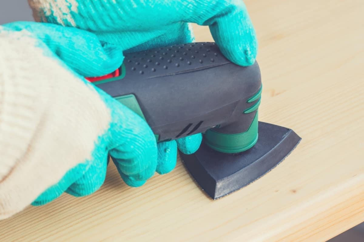 A close up of someone using a detail sander to sand a piece of wood