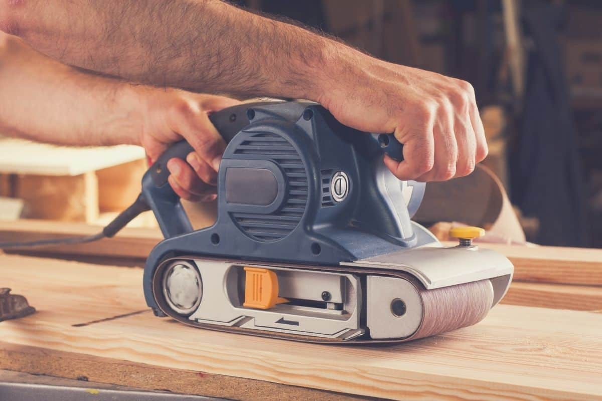 A man using a hand-held belt sander to sand a piece of flat wood.
