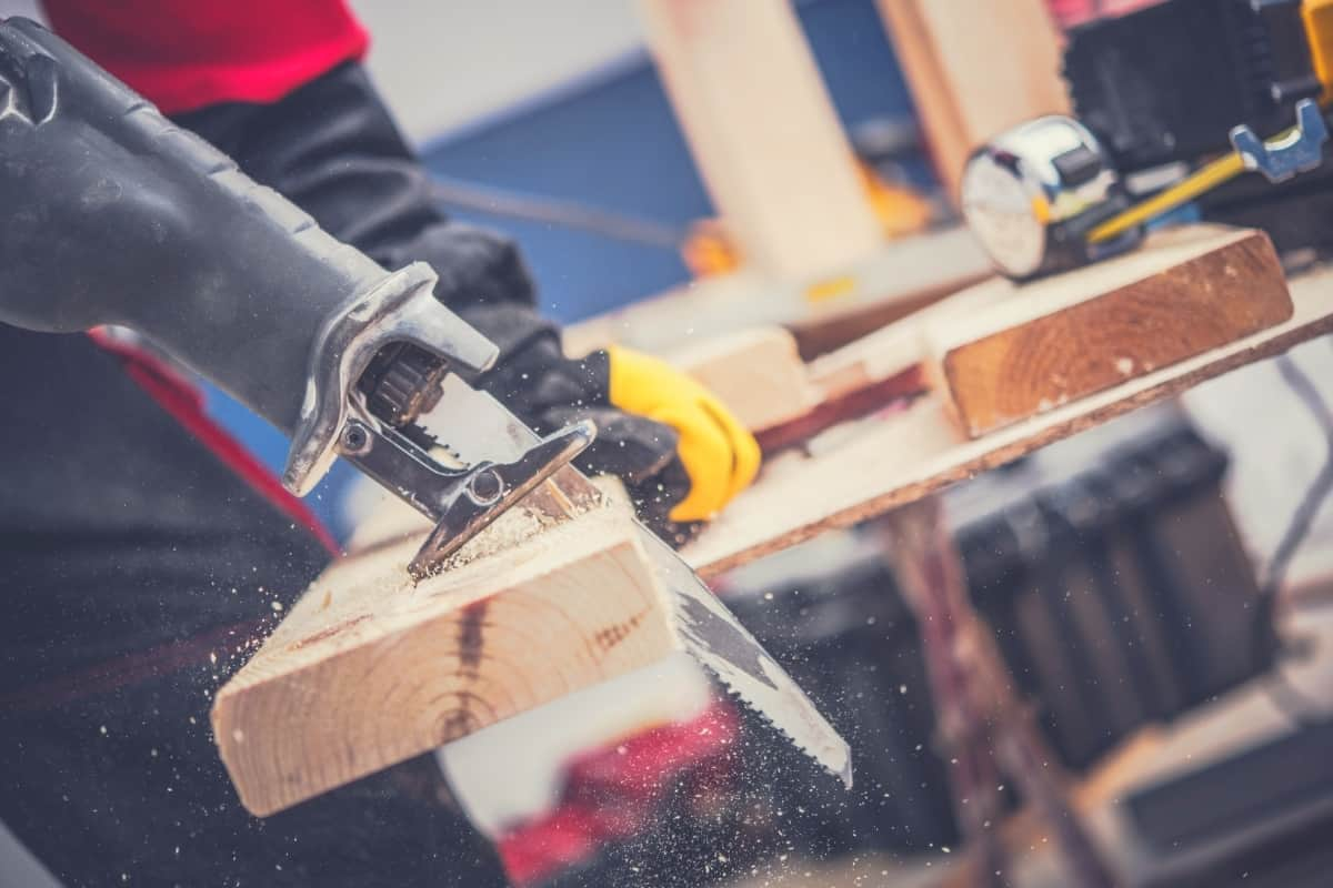 A close up image of someone cutting a piece of timber with a reciprocating saw