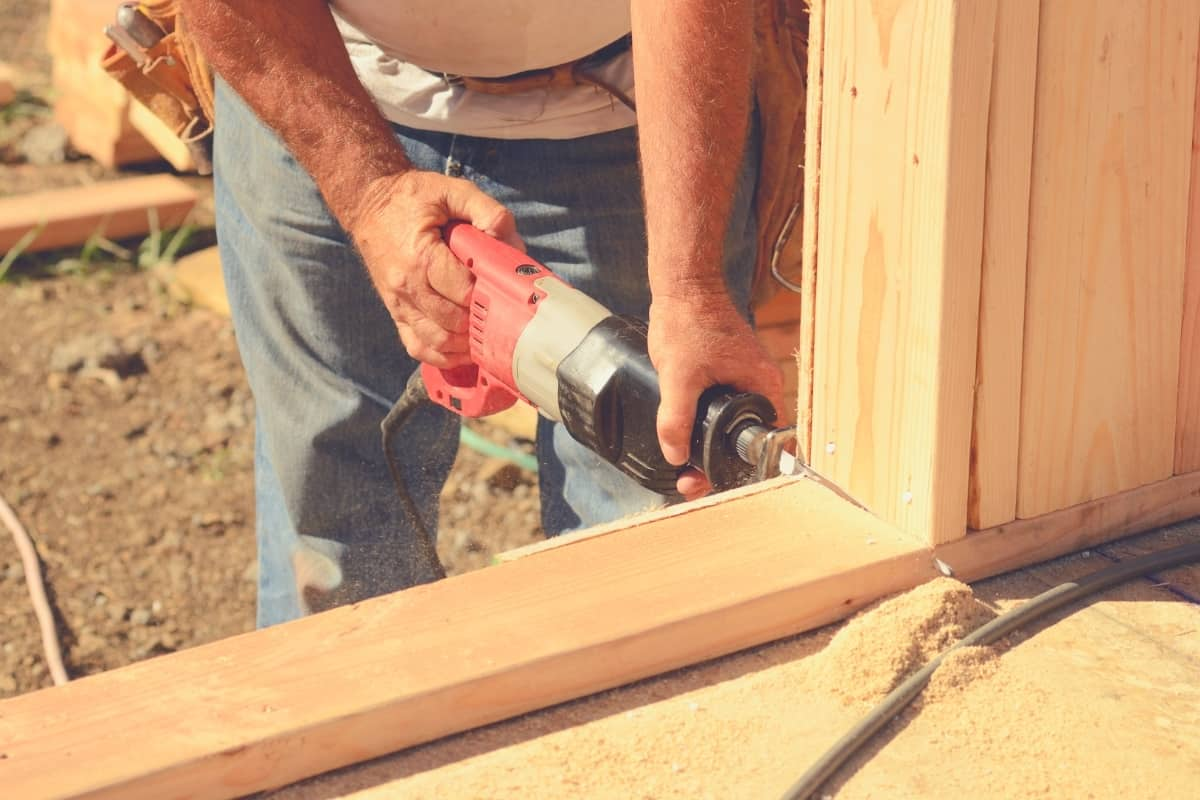 A man cutting some timber framing with a reciprocating saw